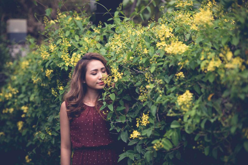 Жена се наслаждава на аромата на растение
