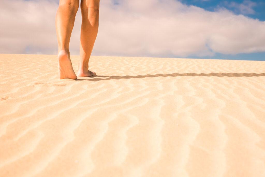 Женаски крака ходят боси по пясъка