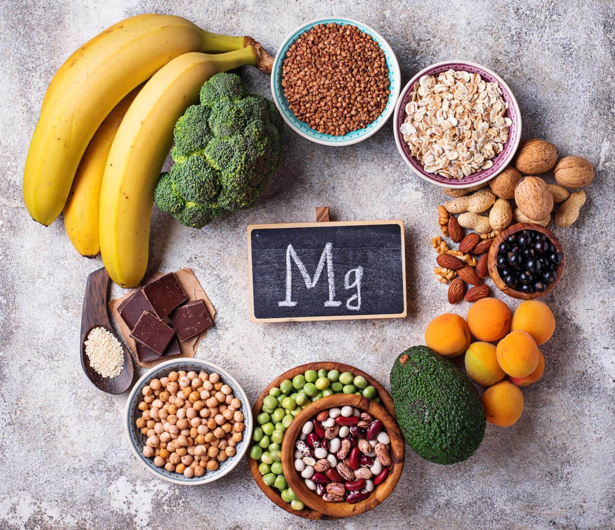 Храни съдържащи магнезий около табелка с името на химичният елемент.