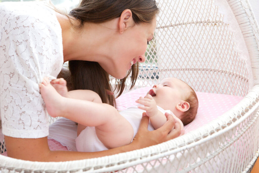 Млада жена се радва на бебето си.